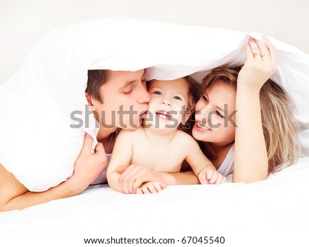 A beautiful couple with Baby on bed. Stock photo © Lopolo