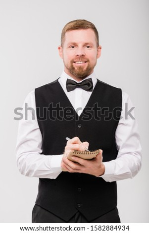 Happy young waiter in bowtie and black waistcoat writing down order of client Stock photo © pressmaster