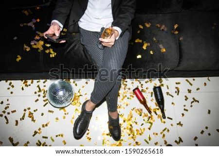 Low section of young elegant man with smartphone and flute of champagne Stock photo © pressmaster