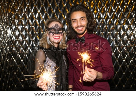 Happy girl in venetian mask and guy with sparkling bengal lights looking at you Stock photo © pressmaster