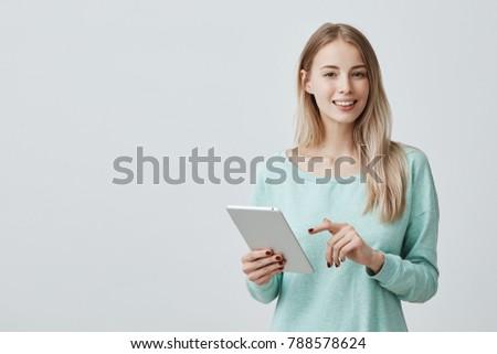 Pretty female entrepreneur with long dark hair, works on computer, develops strategy of advertising  Stock photo © vkstudio