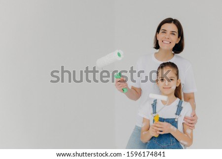 Smiling caring mother embraces daugher, stands with paint rollers, paint walls in house, girl has di Stock photo © vkstudio