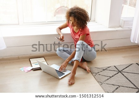 Indoor shot of attractive woman leans to laptop computer, focused into screen, surfes internet, sear Stock photo © vkstudio