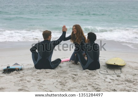 Rear vew of multi-ethnic group of friends sitting and interacting with each other while giving high  Stock photo © wavebreak_media