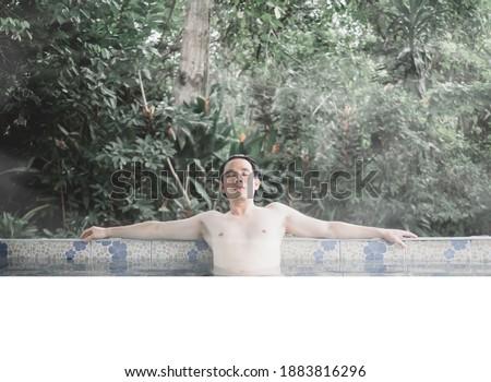 Geothermal spa. Man relaxing in hot spring pool. Young man enjoying bathing relaxed in a blue water  Stock photo © galitskaya