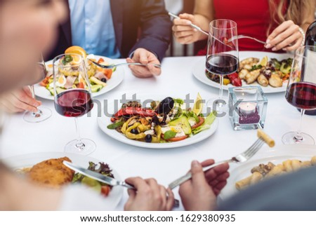Four friends eating Italian food in fancy restaurant, close-up Stock photo © Kzenon
