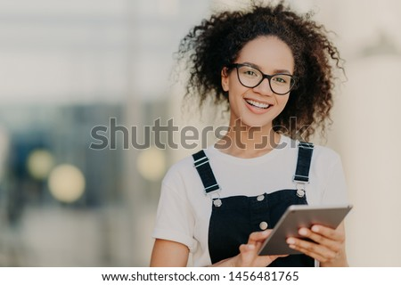 Lovely dark skinned ethnic woman with crisp hair combed in pony tail, smiles gently, wears optical g Stock photo © vkstudio