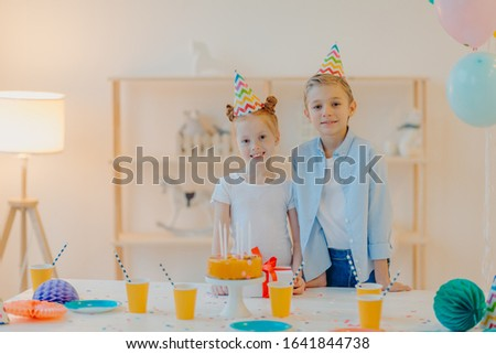 Glad boy and his small ginger sister dressed in festive clothes, party hats, celebrate birthday toge Stock photo © vkstudio
