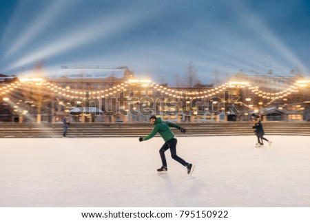 Active sorty male has fun in outdoor park on ice rink decorated with garlands, shows his talents of  Stock photo © vkstudio