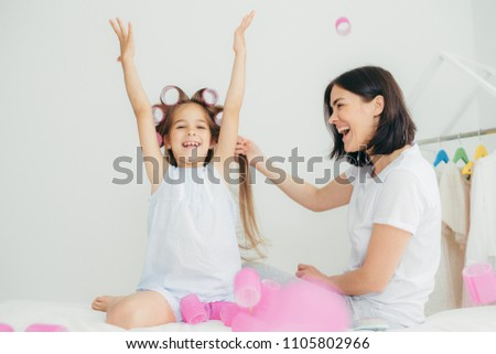 Cheerful brunette female does hair of her daughter who has glad expression, raised hands and has cur Stock photo © vkstudio