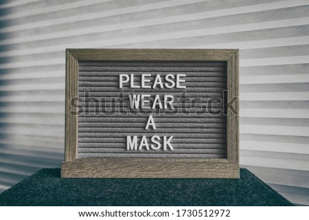 COVID-19 sign PLEASE WEAR A MASK at grocery store entrance for coronavirus prevention. Message on pi Stock photo © Maridav