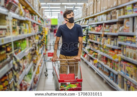 Alarmed man wears medical mask against coronavirus while grocery shopping in supermarket or store- h Stock photo © galitskaya