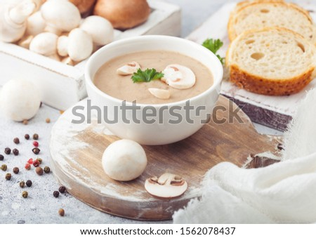 Wooden plate of creamy chestnut champignon mushroom soup with wooden spoon, pepper and kitchen cloth Stock photo © DenisMArt