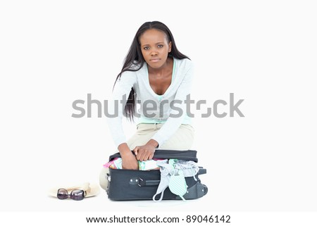 Stock photo: Young woman having problems packing her suitcase against a white background