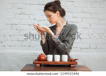 young woman sitting in meditation pose in front of tea set rela stock photo © hasloo
