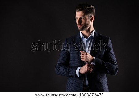 portrait of a confident young male executive buttoning his cuff stock photo © hasloo