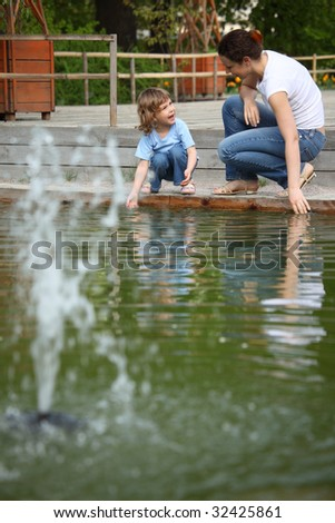 Mother with daughter in park at pool with fountain touch water Stock photo © Paha_L