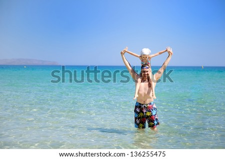 Happy family with little girl standing knee-deep in sea on beach stock photo © Paha_L