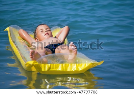 boy in dark blue swimming trunks relaxing on an inflatable mattr Stock photo © Paha_L