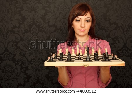 Portrait of girl in red shirt with chessboard against the wall with ornament.  Horizontal format. Stock photo © Paha_L