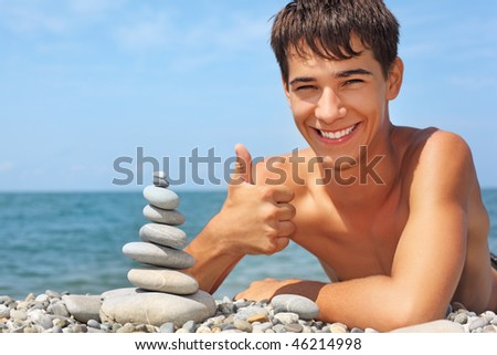 teenager boy lying on stony seacoast, creates pyramid from pebbl Stock photo © Paha_L