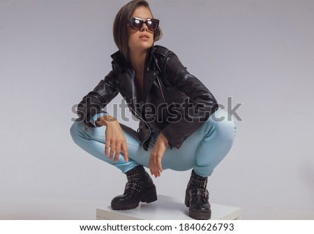 girl in leather jacket posing seated while looking at the camera Stock photo © feedough