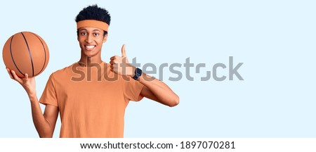 African sports man holding basket ball and showing okay gesture Stock photo © deandrobot