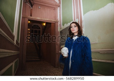 Young lady standing indoors at night. Holding artificial skull. Stock photo © deandrobot