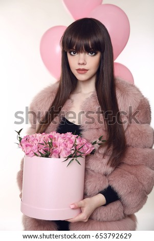 young brunette girl in pink fur coat with rose bouquet of flower stock photo © victoria_andreas