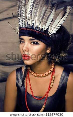 Stock photo: young pretty woman with make up like North American indian, feather in hair, fashion halloween conce