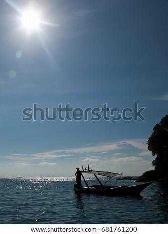 Man standing on docked boat in sunlight, Tioman Island, Malaysia Stock photo © IS2