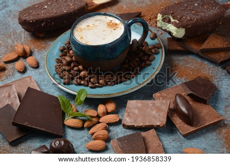 gelato pops with milk chocolate and coffee beans on a wooden stick over stone iced table top view stock photo © artjazz