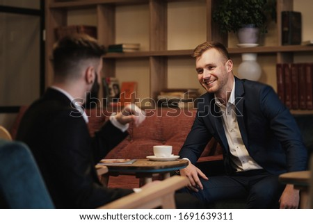 Handsome happy man sitting at table in restaurant and proposing  Stock photo © deandrobot