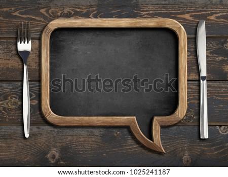 Vintage kitchen wooden utensils with chalk menu board on black stone table background. Top view. Stock photo © DenisMArt