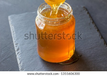 Wooden stick on a spilled honey on the table and glass pot with natural meadow sweet dessert on a gr Stock photo © artjazz