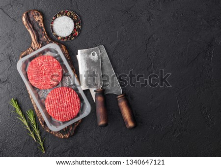 Stock photo: Plastic tray with raw minced homemade beef burgers with spices and herbs. Top view with space for te