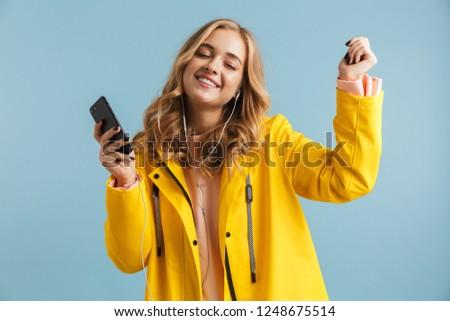image of stylish woman 20s wearing raincoat holding mobile phone stock photo © deandrobot