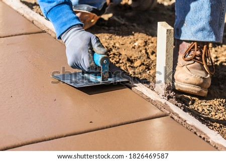Construction Worker Smoothing Wet Cement With Hand Edger Tool Stock photo © feverpitch