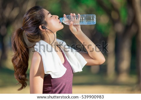 Attractive sporty woman drinking water from a bottle after jogging or running Stock photo © galitskaya