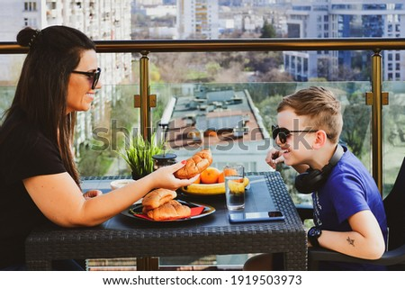 The boy is having breakfast on the balcony. Breakfast table with coffee fruit and bread croisant on  Stockfoto © galitskaya
