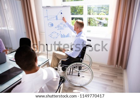 disabled young businessman giving presentation to his colleague stock photo © andreypopov