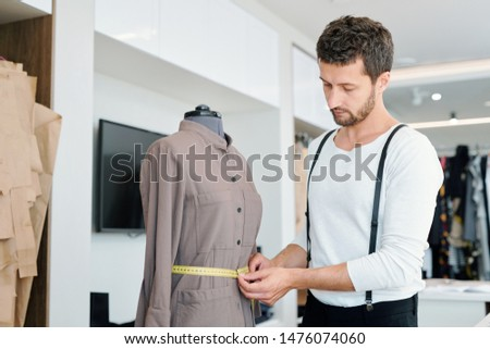Young man measuring waist of female jacket on mannequin in workshop Stock photo © pressmaster