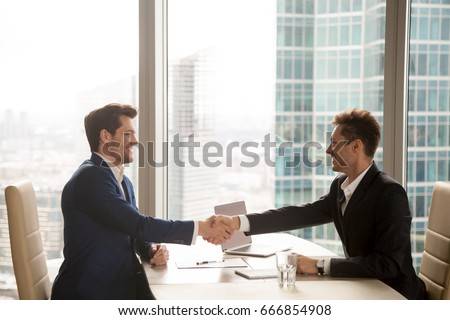 Two smiling businessman shaking hands together after good deal c Stock photo © Freedomz