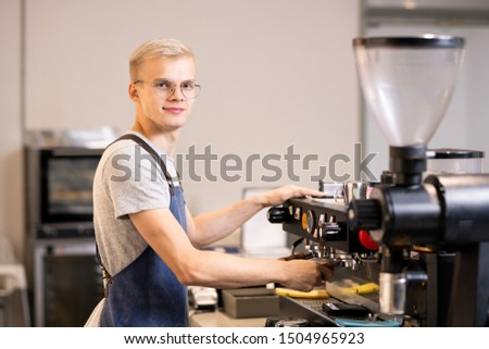 Successful barista in uniform using coffee machine while standing by workplace Stock photo © pressmaster