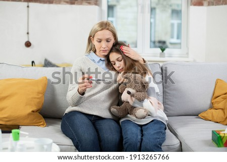 worried mother with thermometer sitting on bed by her sick little daughter stock photo © pressmaster