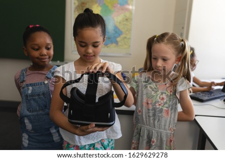 Front view of schoolgirl with curious classmates holding a virtual reality headset in classroom of e Stock photo © wavebreak_media