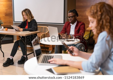 Stock photo: Group of multicultural students using mobile gadgets while preparing homework