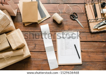 Top view of checklist order surrounded by packed gifts and wrapping items Stock photo © pressmaster