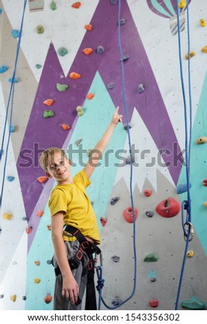 happy schoolboy in activewear standing in front of camera while pointing upwards stock photo © pressmaster