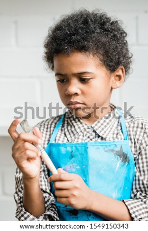 african schoolboy in blue apron looking at paintbrush during work in studio stock photo © pressmaster
